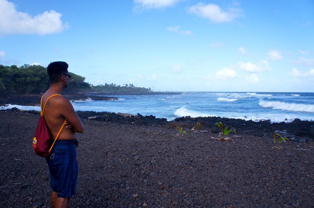 Watching waves crash and tumble black pebbles while making black sand at Isaac Hale Beach Park.