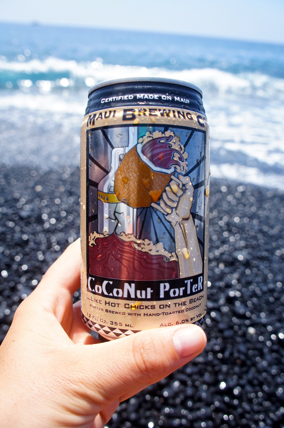 Drinking some local Coconut Porter beer from Maui Brewing Company on a black pebble beach on the Big Island, Hawaii.